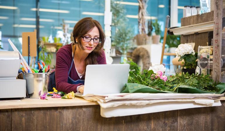 UK Florist using her laptop inside her flower shop