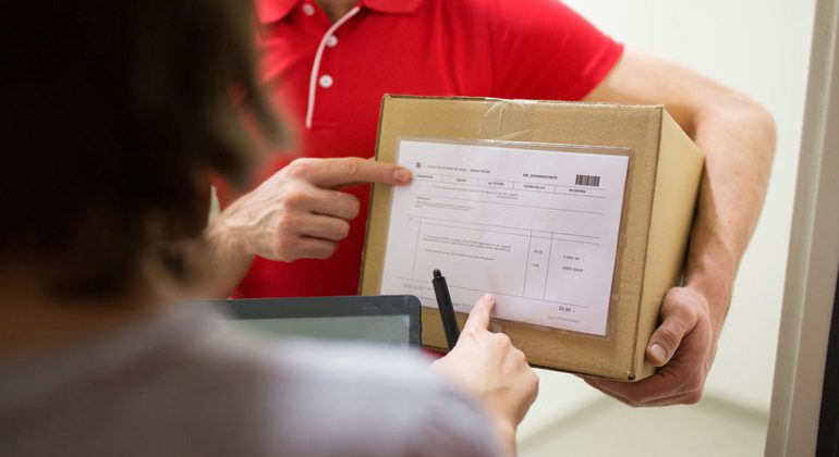 Courier Dispatch Driver Holding a Parcel Box and Pointing Towards an Invoice