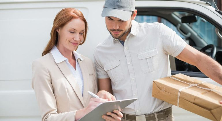 dispatch driver holding a package and a woman customer signing order received delivery form