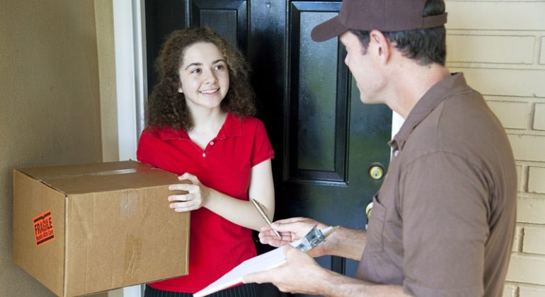 Delivery man giving a package to a customer