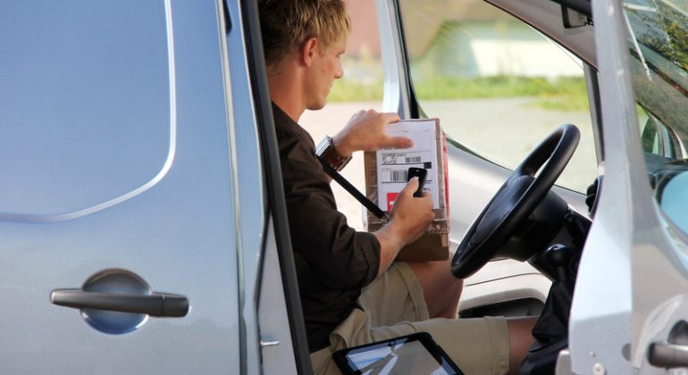 Courier Driver inside a van scanning order delivery confirmation
